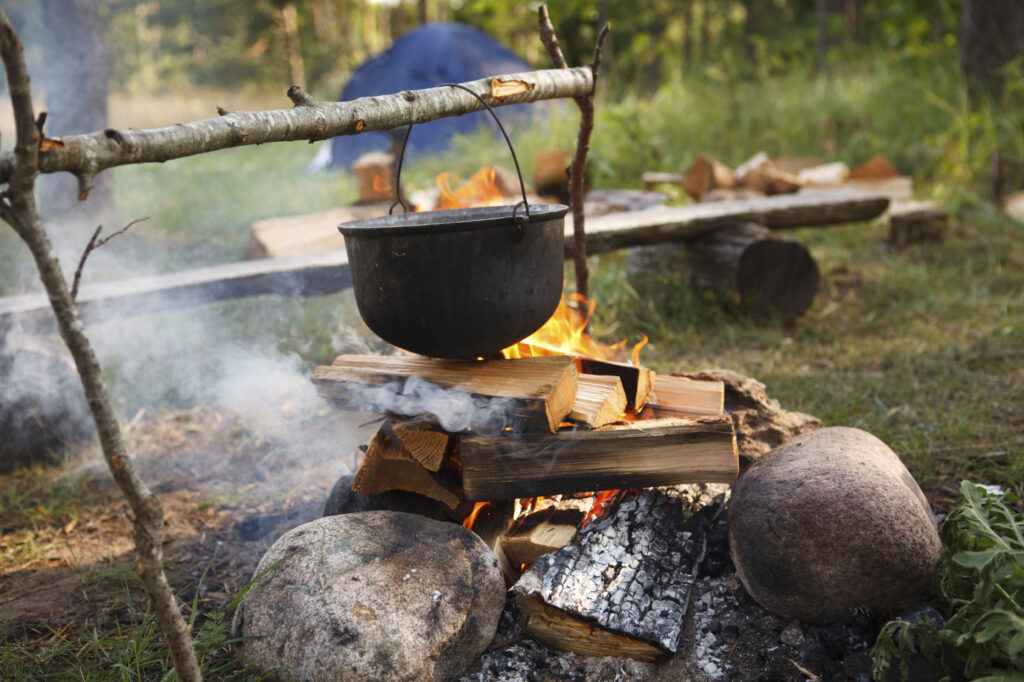 Cooking survival food in a pot suspended over an open fire in the outdoors.