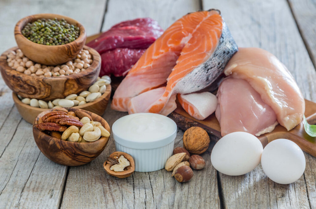 salmon, nuts, eggs, chicken, and other high-protein foods on a wood table